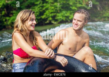 Ein junges Paar Röhren einen Fluss hinunter. - Stockfoto