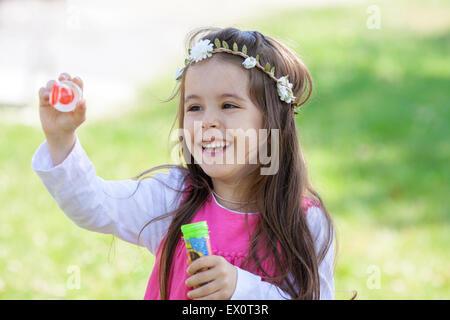 Schönes Porträt von Süße schöne kleine Mädchen bläst Seifenblasen im Park, im Sommer - Stockfoto