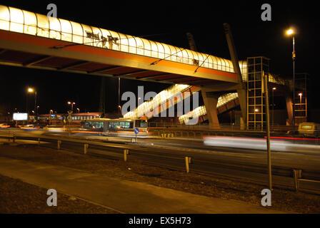 Eine Fußgängerbrücke hell erleuchtet in der Nacht. - Stockfoto
