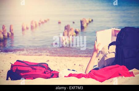 Vintage getönten Foto von unerkennbar Person liest Buch am Strand. - Stockfoto