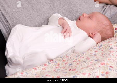 Neugeborenes Babymädchen neben ihrer Mutter schlafen hinlegen - Stockfoto