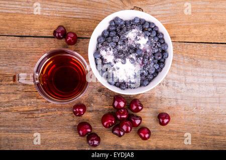 Tasse Tee süßen Kirschen und Blaubeeren in Schüssel auf einem hölzernen Hintergrund weiß - Stockfoto