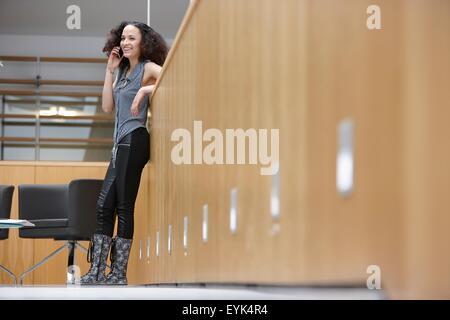 Geschäftsfrau im Chat auf Smartphone im Büro - Stockfoto