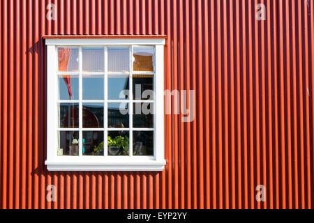Rote Wand aus Wellblech und ein weißes Fenster - Stockfoto
