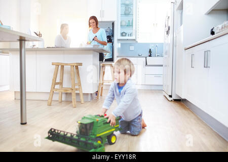 Frauen in Küche kochen, während junge mit Spielzeug-Traktor auf Etage spielt - Stockfoto