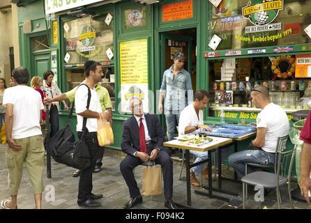 Menschen sitzen auf Stühlen vor dem Restaurant im Marais, Paris, Frankreich - Stockfoto
