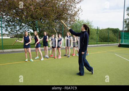Studenten und Schlagball Coach auf Feld - Stockfoto