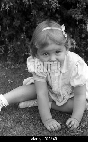 Ein junges Mädchen sitzen auf dem Rasen nach oben auf die Kamera. - Stockfoto