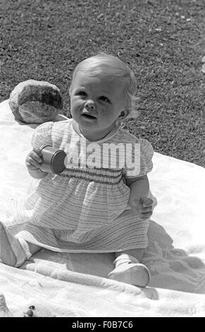 Ein kleines Baby sitzen auf der Decke in einem Garten. - Stockfoto
