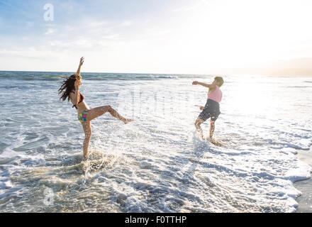 Junges Paar am Strand, im Meer herumalbern - Stockfoto
