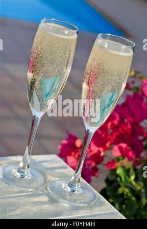 Alfresco Gläser Champagner auf der sonnenbeschienenen Terrasse Tisch mit Bougainvillea Blumen und Swimmingpool hinter - Stockfoto