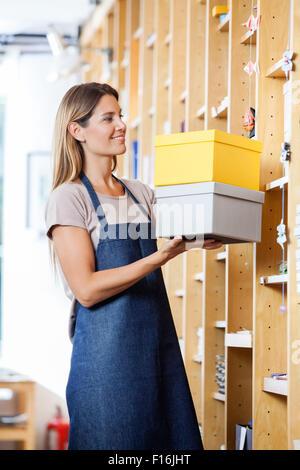 Verkäuferin, die Kartons In Regalen zu halten - Stockfoto