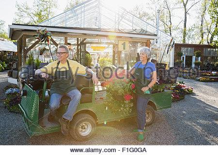 Arbeitnehmer mit hängenden Blumenkorb in Warenkorb außerhalb Gewächshaus - Stockfoto