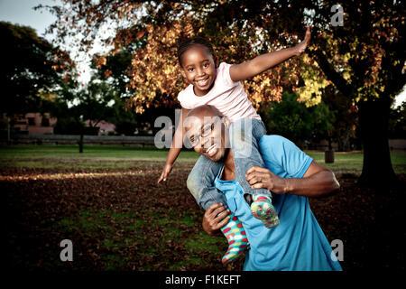 Young African Vater spielen in einem Park mit seiner Tochter - Stockfoto
