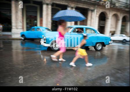 Havanna, Kuba - 13. Juni 2011: Kubanische Mutter und Kind die Straße überqueren vor Vintage American Taxi Auto an - Stockfoto