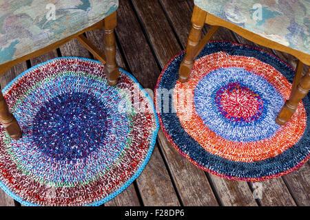 Zwei handgefertigten bunten Teppichen auf einem Holzboden mit ein paar Stühle - Stockfoto