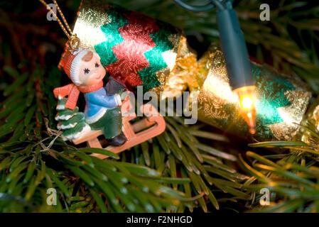 eine lustige und niedliche Weihnachtsdekoration in Form eines kleinen Jungen auf einem Schlitten neben einem kleinen - Stockfoto