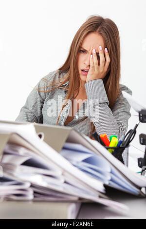 Porträt des jungen schönen Business-Frau, umgeben von großen Stapel von Dokumenten. - Stockfoto