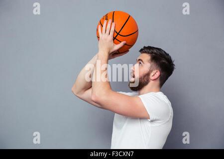 Porträt eines jungen Mannes lesen, Basketball über grauen Hintergrund zu werfen - Stockfoto