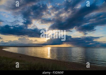 Sonnenuntergang Strahlen durch dramatische Wolken über ruhige See und Strand - Stockfoto