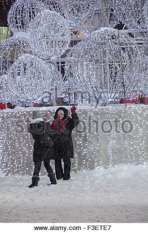 Frauen fotografieren in der Nähe von einem Weihnachtsbaum Struktur Struktur der Welt-wie Kugeln, dekoriert mit Farbwechsel - Stockfoto