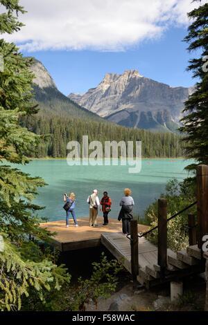 Touristen bewundern die Aussicht von einer Promenade am Emerald Lake im Yoho Nationalpark, Britisch-Kolumbien, Kanada - Stockfoto