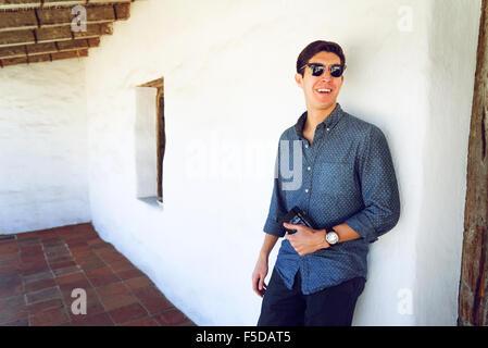 Ein junger lässige Geschäftsmann lächelnd eine Wand gelehnt - Stockfoto