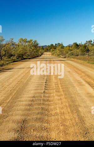 Lange gewellte Straße schneidet durch Buschland des Aroona Tal in Flinders Ranges, unter blauem Himmel im Outback - Stockfoto