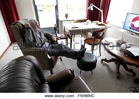 älterer Mann entspannt im Sessel vor dem Fernseher - Stockfoto