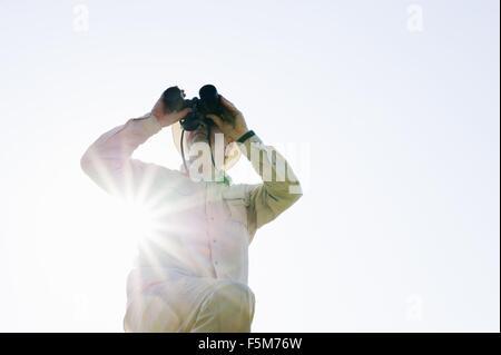Niedrigen Winkel Ansicht der ältere Mann im Sonnenlicht durch ein Fernglas schauen - Stockfoto