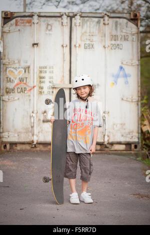 Schweden, Vastergotland, Lerum, Porträt eines jungen (8-9) mit Skateboard vor dem Tor - Stockfoto