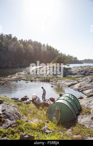 Schweden, Westküste, Bohuslan, Flato, Mann camping am Ufer - Stockfoto