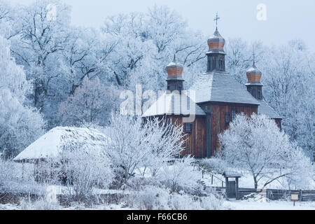 eine alte Kirche aus Holz unter den Bäumen im Schnee - Stockfoto