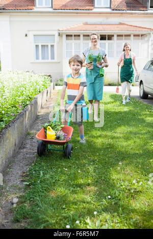 Junge drängen Schubkarre mit Pflanzen im Gemüsegarten - Stockfoto