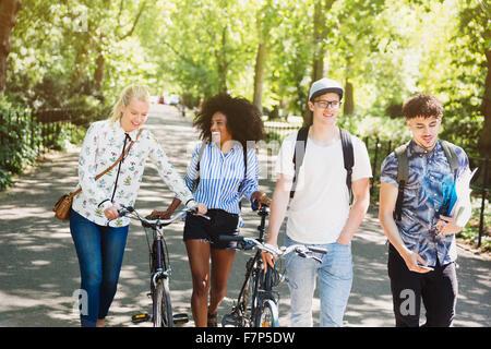 Freunde zu Fuß mit dem Fahrrad im park - Stockfoto