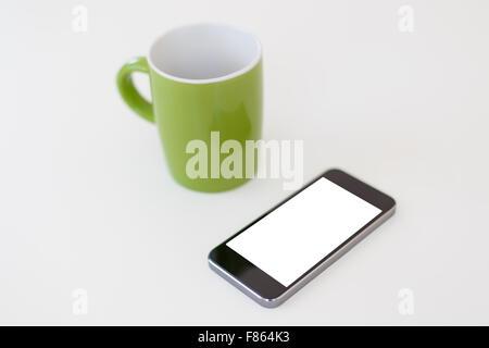 Detailansicht eines smart phone, mit weißen leere Kopie Raum Bildschirm, in der Nähe von einem grünen Becher auf - Stockfoto