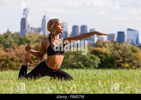 Vorderansicht der junge Frau kniet auf dem Rasen Dehnung Bein in Yogaposition, Arm aus, wegsehen, Philadelphia, - Stockfoto