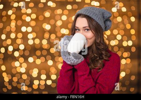 Schöne Locken junge Frau im grauen Hut und Handschuhe trinken heißen Schokolade über glitzernden Hintergrund - Stockfoto