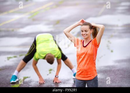 Junges Paar stretching nach dem Lauf auf Asphalt bei Regenwetter - Stockfoto