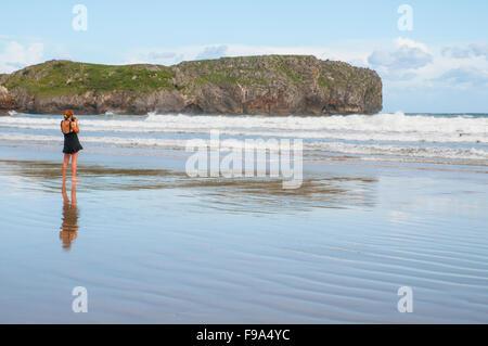 Frau, die das Fotografieren in Torimbia Strand. Niembro, Asturien, Spanien. - Stockfoto