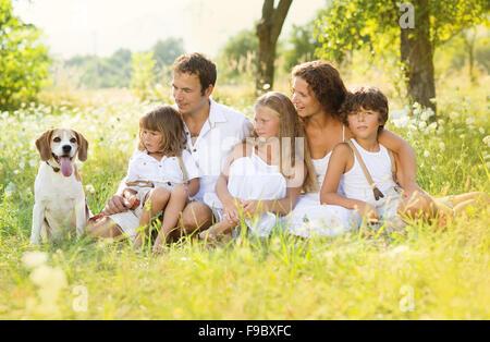 Glückliche junge Familie verbringt Zeit im Freien im Sommer - Stockfoto