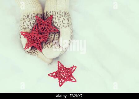 Frau Händen im Licht blaugrün gestrickte Handschuhe halten rote Sterne auf Schnee Hintergrund. Winter und Weihnachten - Stockfoto