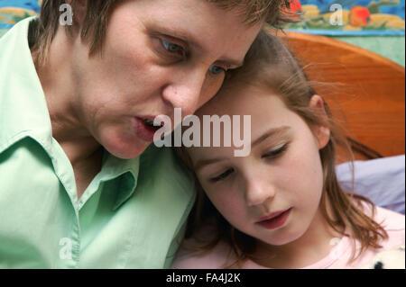 Alleinerziehende, die eine Gutenachtgeschichte zu ihrer kleinen Tochter zu lesen, - Stockfoto