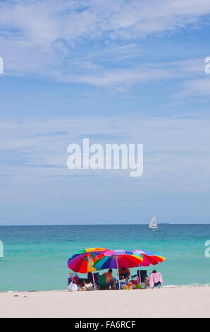 Gruppe von Personen unter bunten Sonnenschirmen am Strand.  (Foto von Sean Drakes/Alamy) - Stockfoto