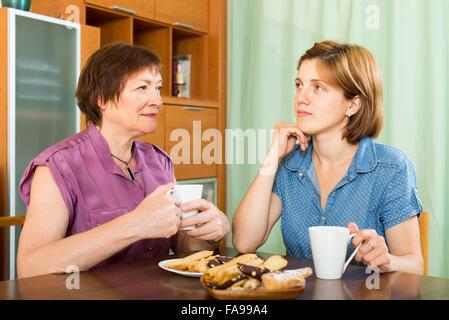 Ältere Frau im Gespräch mit ihrer kleinen Tochter und beim Tee trinken - Stockfoto