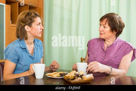 Junges Mädchen und ihre betagte Mutter Teetrinken am Tisch und reden - Stockfoto