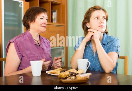 Rentner-Mutter und ihre Tochter Tee trinken und eine Diskussion - Stockfoto