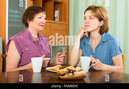 Junges Mädchen und Mutter Rentner Kaffee zu trinken und eine Diskussion - Stockfoto
