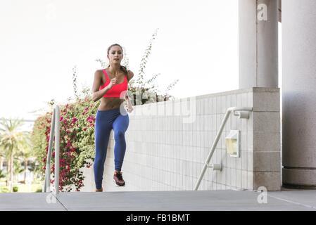 Junge Frau trägt Sport-Bekleidung, Treppe, Blick in die Kamera läuft - Stockfoto