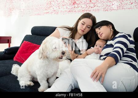 Reife Frau und Tochter mit Babymädchen lesen digital-Tablette auf sofa - Stockfoto